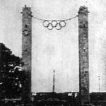 Az olimpiai láng megérkezik a berlini stadionba. Háttérben a marathoni kapu