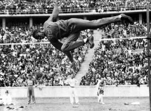 A magasugrás olimpiai  bajnoka Cornelius Johnson a 190 cm-t melegítőruhában ugorja át