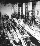 Tengeralattjáró-gyártás Németországban - futószalagon. Az U-hajókon baloldalt most rakják a hajótestre a légkamrákat; a jobboldali hajón már a külső páncélzatot is látni.