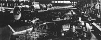 Repülőgépgyár szerelőcsarnoka: a háttérben kétmotoros nagy bombázók állnak még csonka törzzsel, kidolgozatlan szárnyakkal; elöl pedig gyors egymotoros vadászgépeken folyik a szerelés.