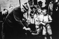 Dr. Karafiáth Jenő titkos tanácsos, főpolgármester pénzt ad egy kisgyermeknek fővárosi kislakások avató ünnepségén