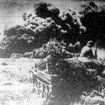 Gépkocsizó-lövészek előnyomulása egy olajvidéken. A háttérben felgyújtott olajtartály füstcsóvája száll a magasba.