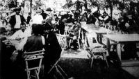 Május elseje. Az emberek a nyári vendéglőket töltik meg, s egy-két pohár sör mellett megbeszélik ügyes-bajos dolgaikat.