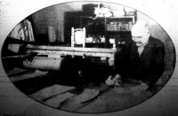 """Elektromos posztó szabó gép a """"csukaüszrke"""" gyártásában. Csuklós kar végén rúd talpán éles acél korongkés fut, amelyet elektromos áram forgat s huz  posztólapból egyszerre hasítja ki a ruha idomait."""