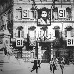 A fasiszta párt főhadiszállása. Óriási méretű  arcképe a Ducének, hatalmas plakátok és SI, azaz Igen jelszó.