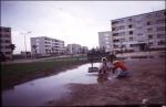 Pocsolya mellett játszadozó gyermekek egy épülő lakótelepen